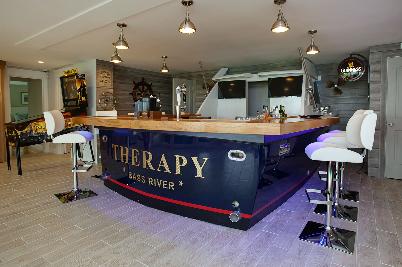 Real-life boat repurposed as a bar for a Cape Cod game room