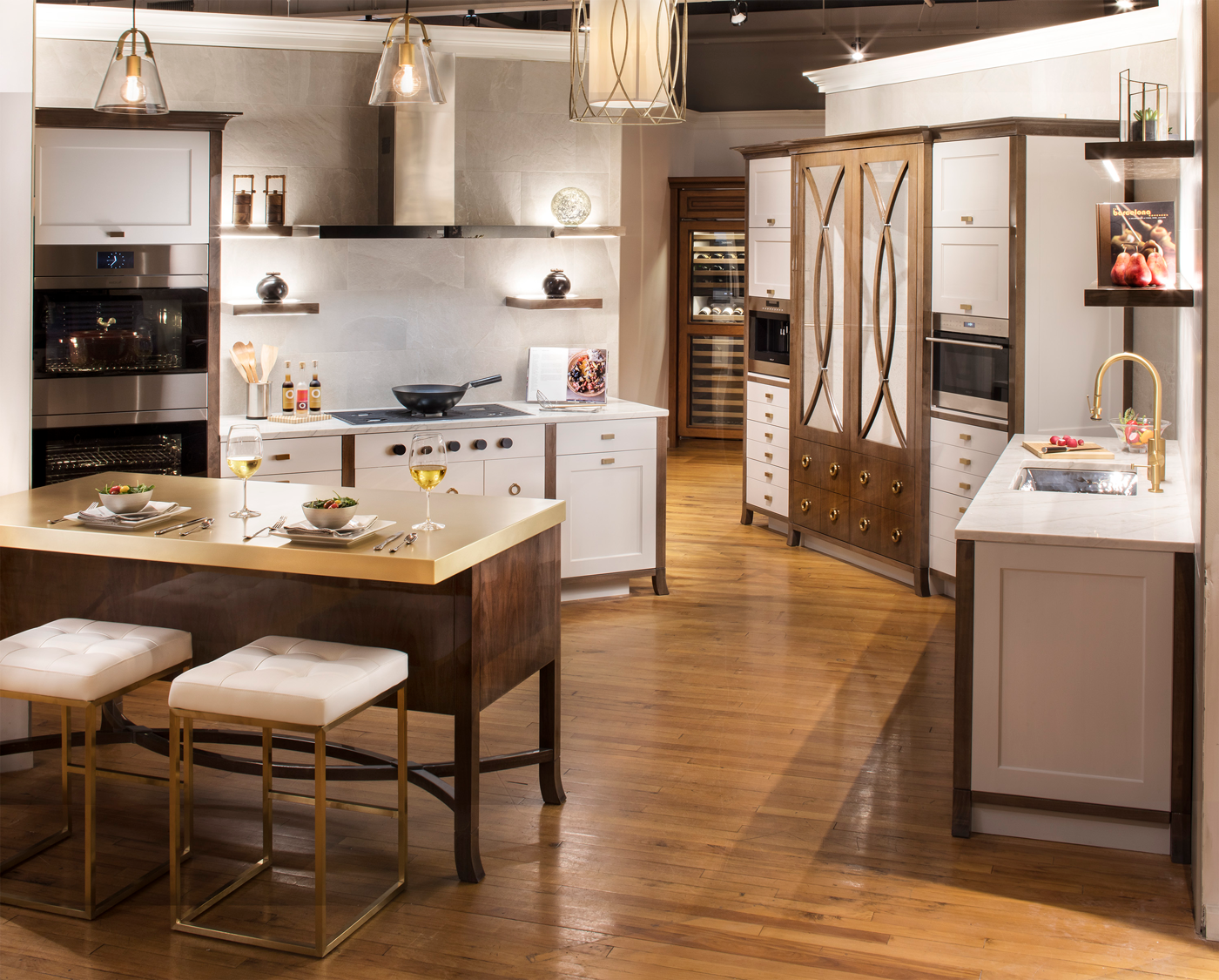 High end kitchen in Clarke showroom with island containing 2 stools and salads and wine