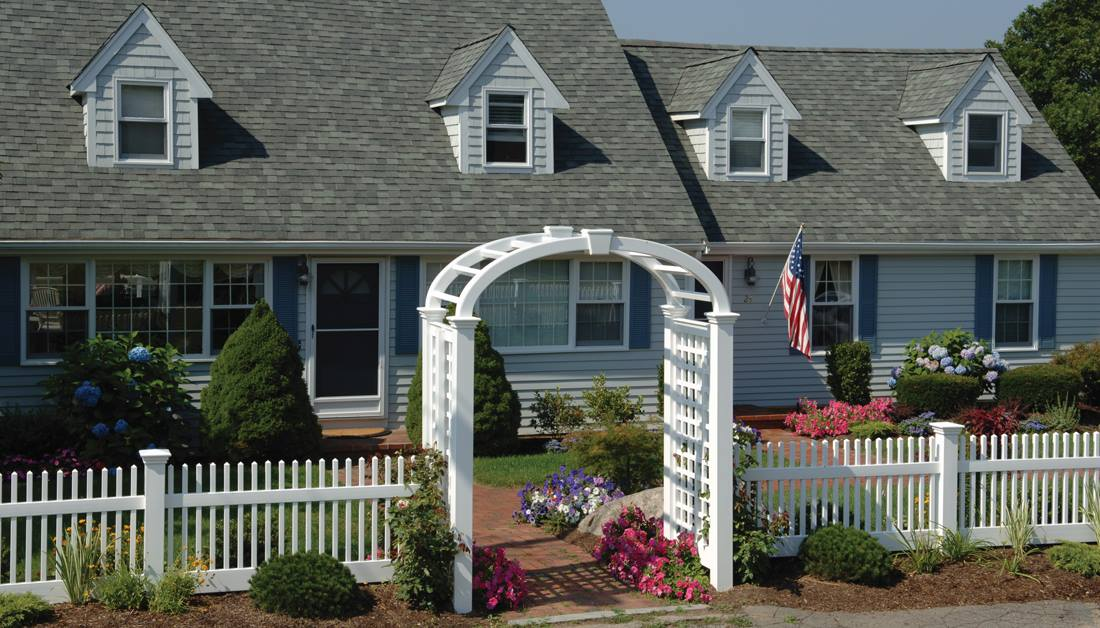 Perfection Fence's Mt. Vernon Line of ForeverVinyl fencing and elliptical Grand Arbor with English Lattice side panels & keystone adornment beautifully enhance the look of this traditional Cape Cod style home.
