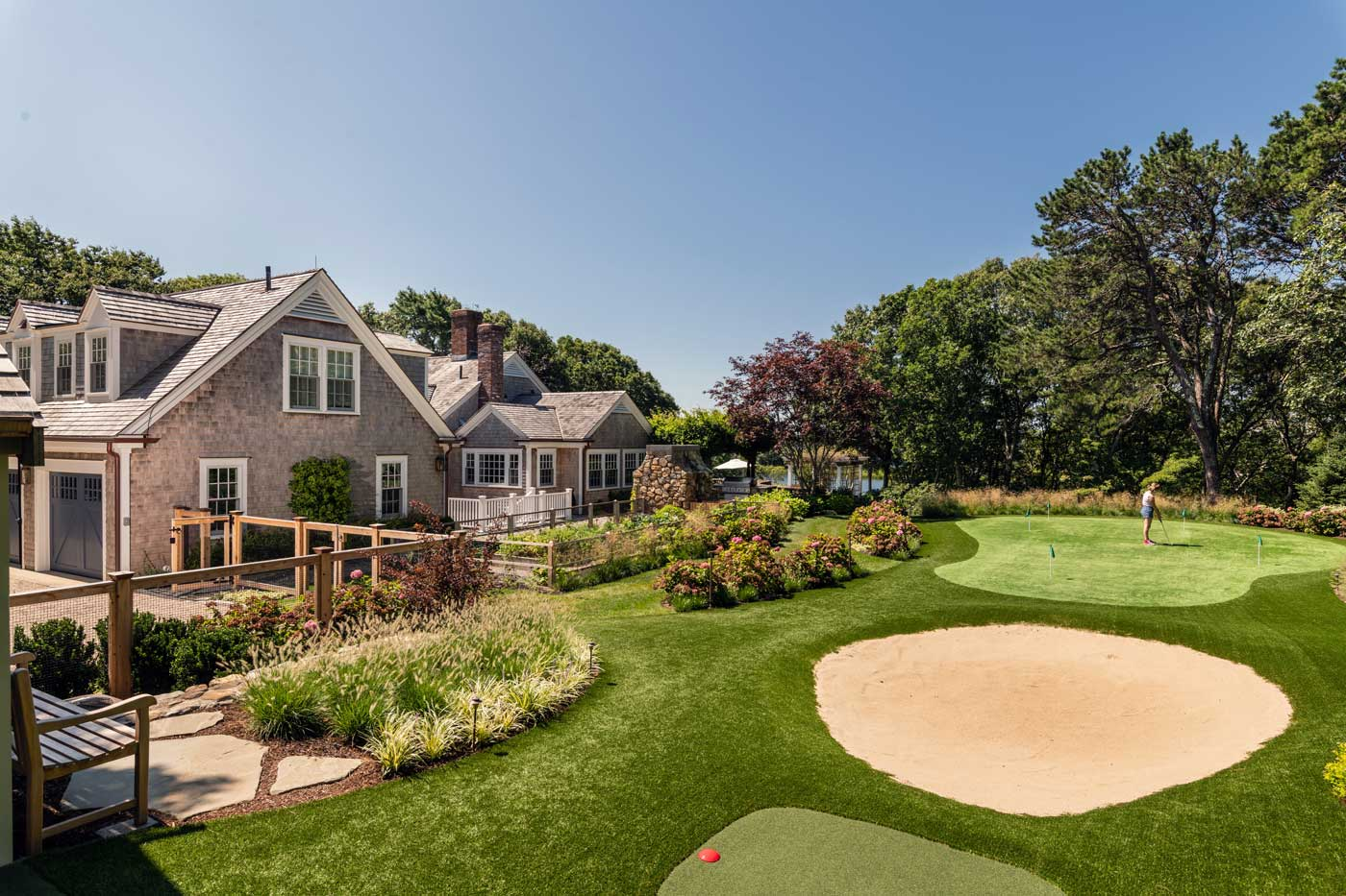golf course with sand trap and person practicing next to a home