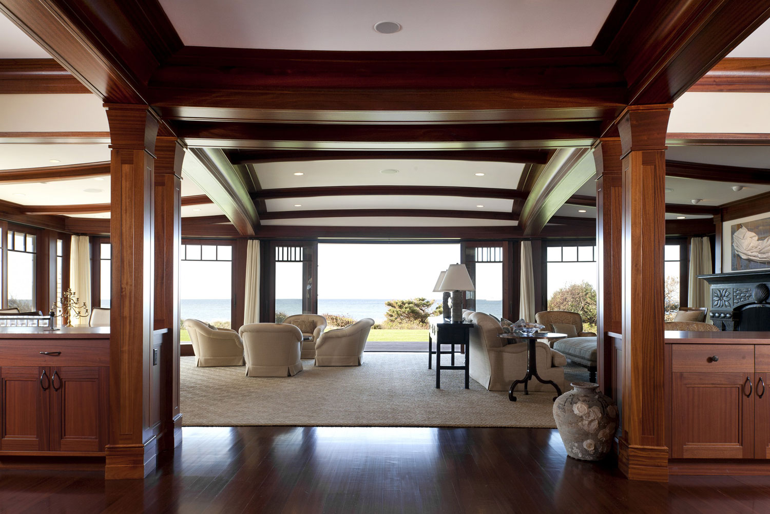 This Great Island House combines the classic Cape & Islands architecture with a more open and tropical interior. Morehouse MacDonald & Associates used figured sapele and carved soapstone mantels in concert with curved planes and elements to subtly reinfor
