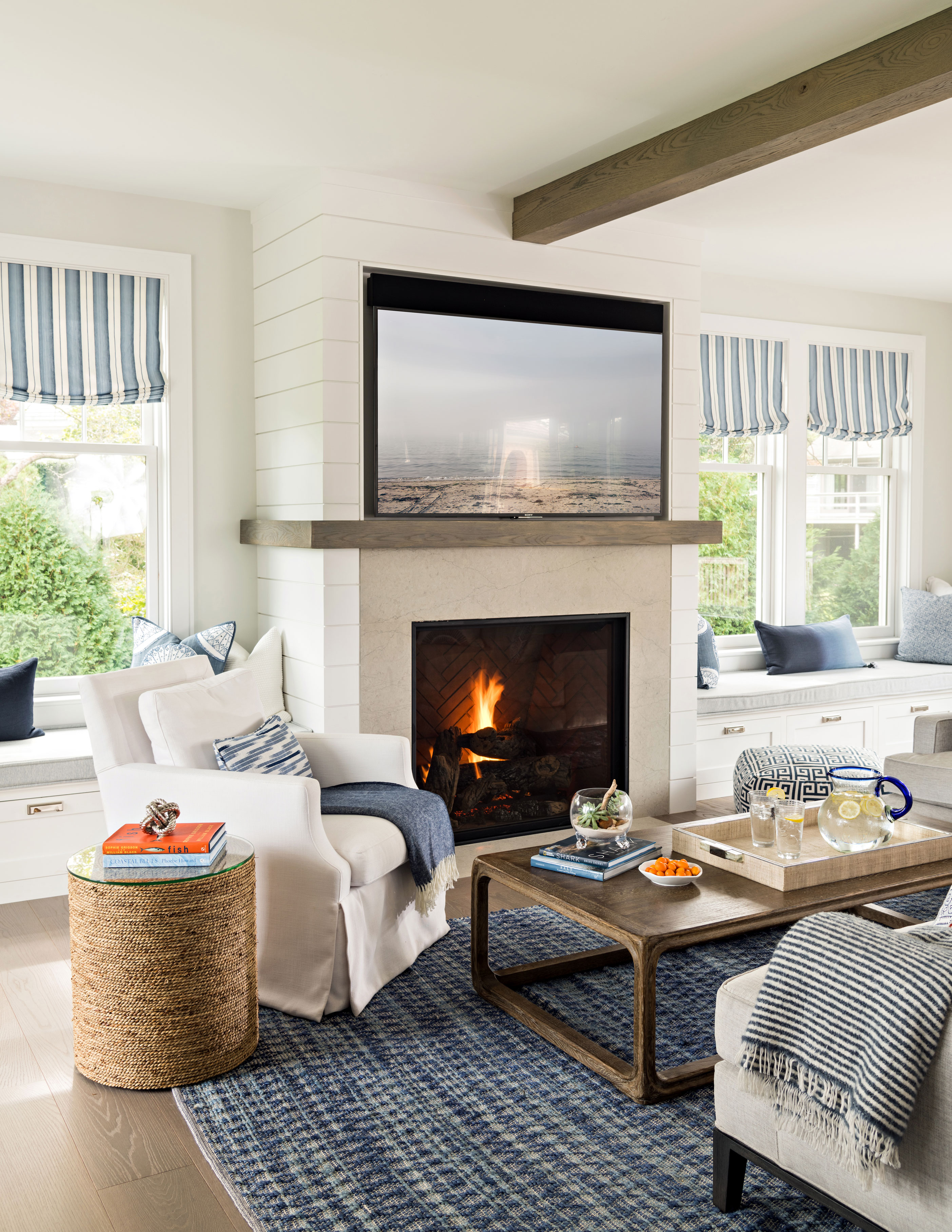 Family room with white furniture and shiplap fireplace with fire burning in fireplace