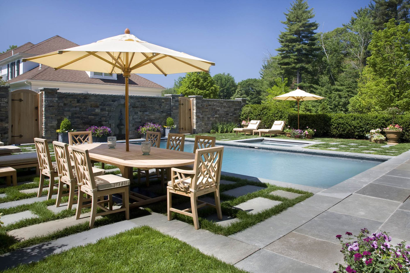Pool with outdoor dining table and lounge chairs
