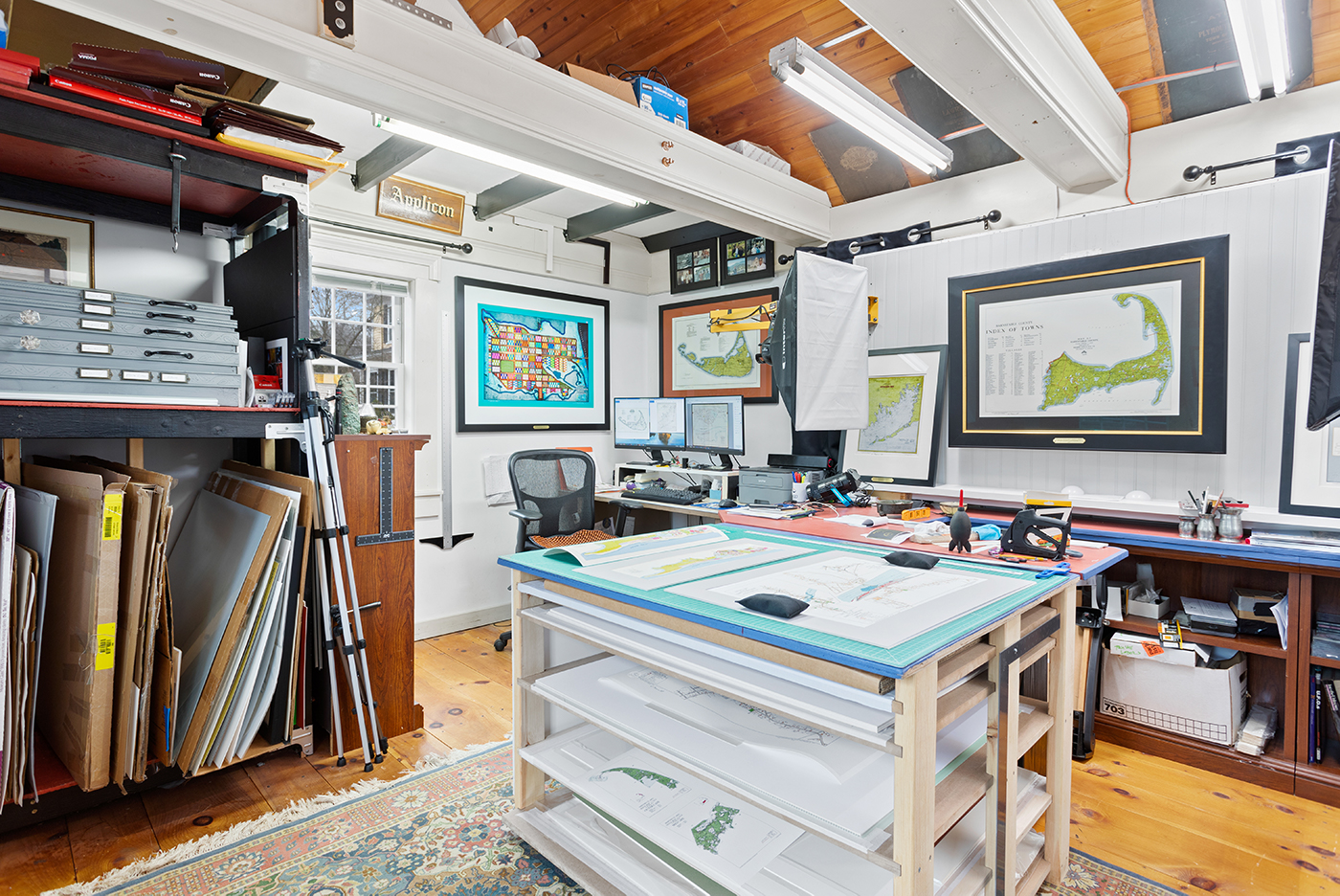 Office with wood ceiling and tray table and maps hanging on the wall