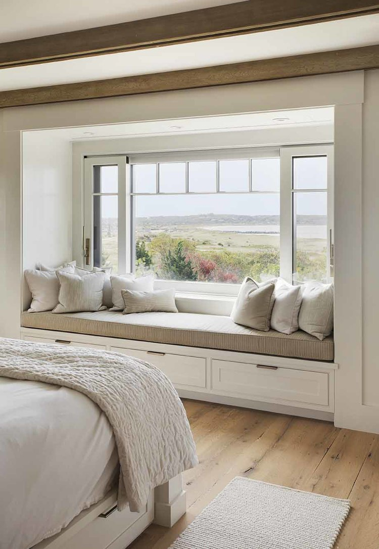 Window seat in bedroom with a view of the water