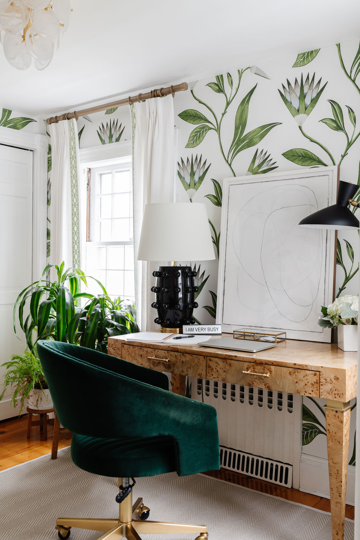 office with small desk green chair and botanical wallpaper