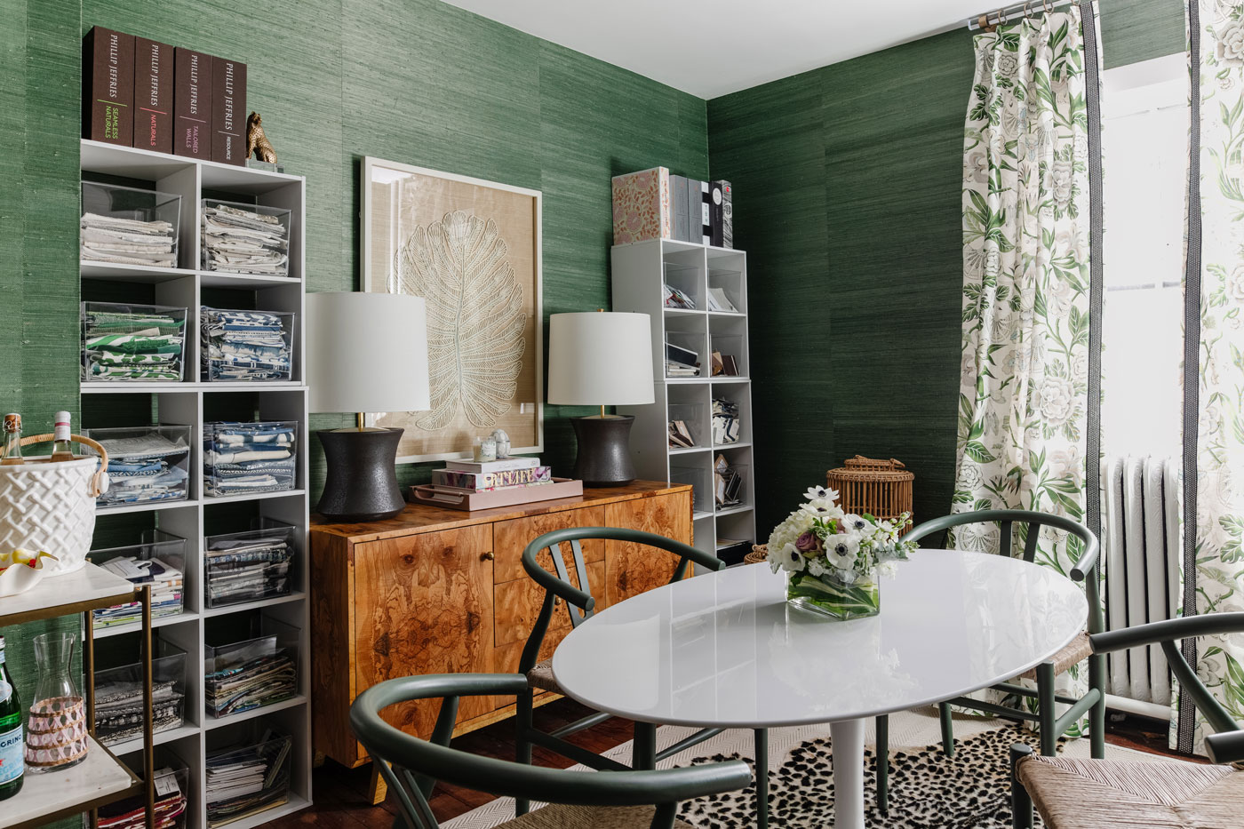 office with oval table in the center and green grasscloth phillip jeffries wallpaper