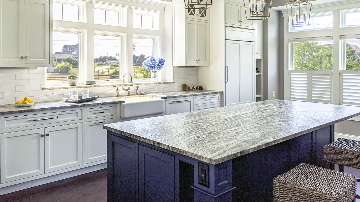 Remodeled white kitchen with blue island and big windows on all sides