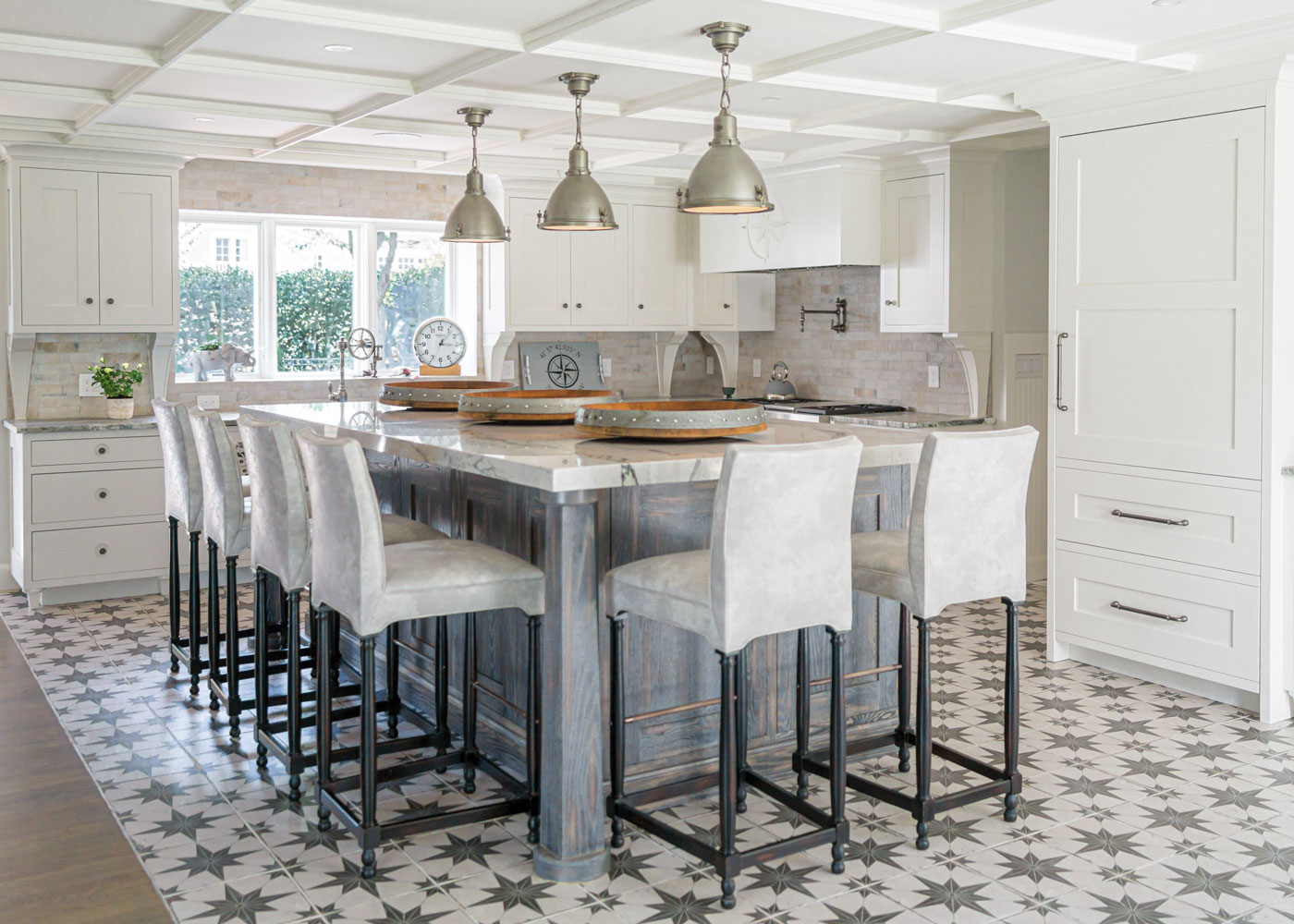 modern kitchen with white cabinets and an oversized island surrounded by stools