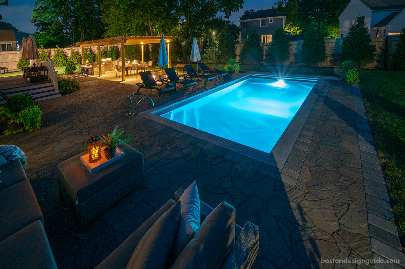 Residential pool terrace design at night by Land Design Associates