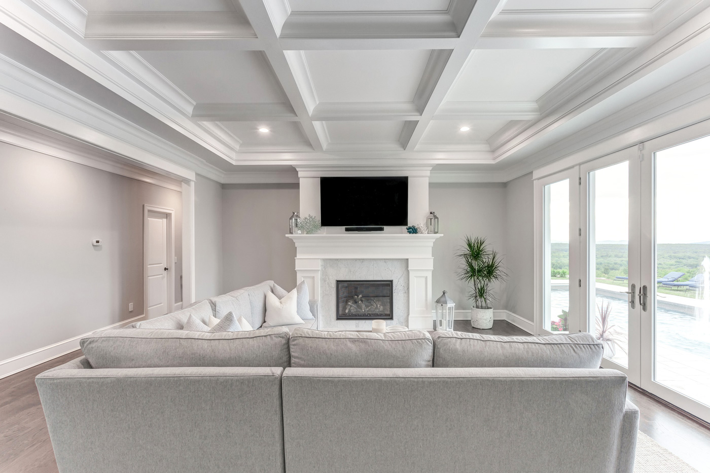 A custom-built mantel and recessed coffered ceiling by Laplante Construction