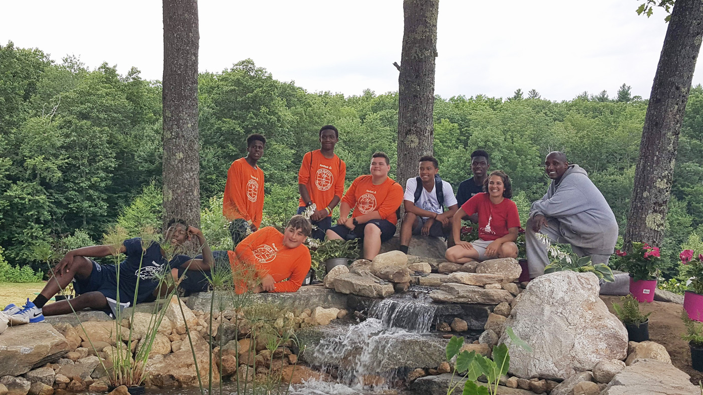 Magma Design Group at Ron Burton Training Village with a group of kids sitting at a waterfall
