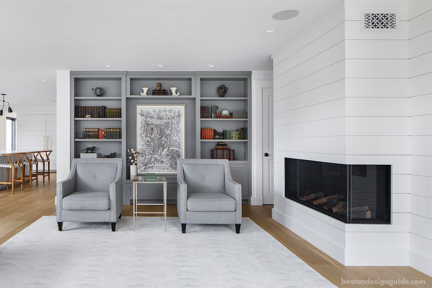 Custom New England living room by custom home builder McCormack Builders with nickel gap wood paneling