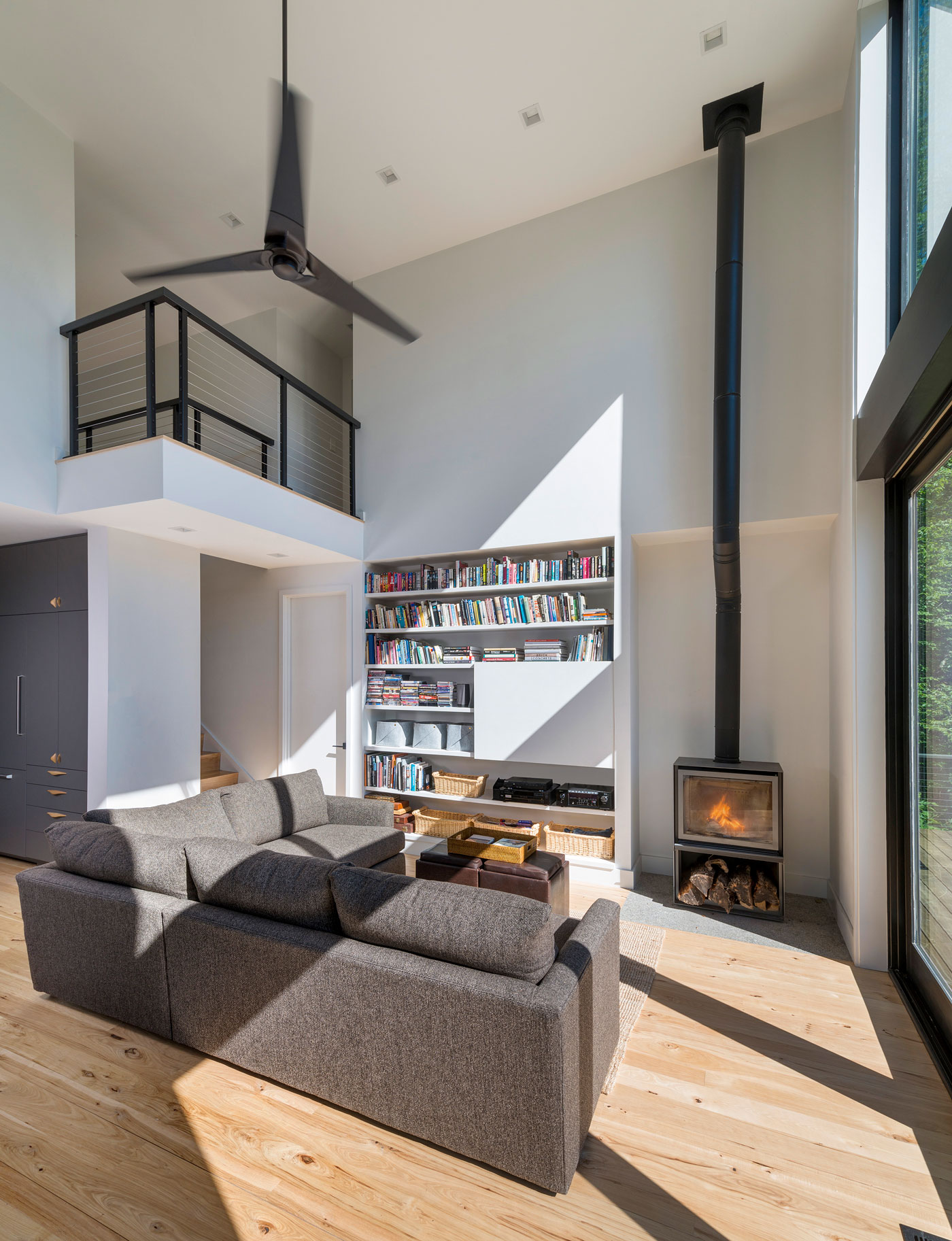 sleek living area with high ceilings a bookcase and a fireplace