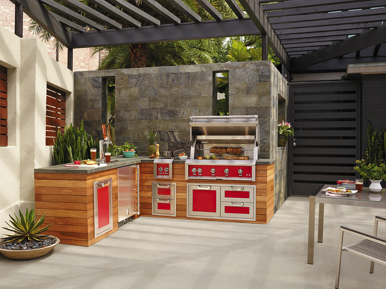 Backyard Patio kitchen with red appliances and a stone countertop with food being prepared and meat being grilled