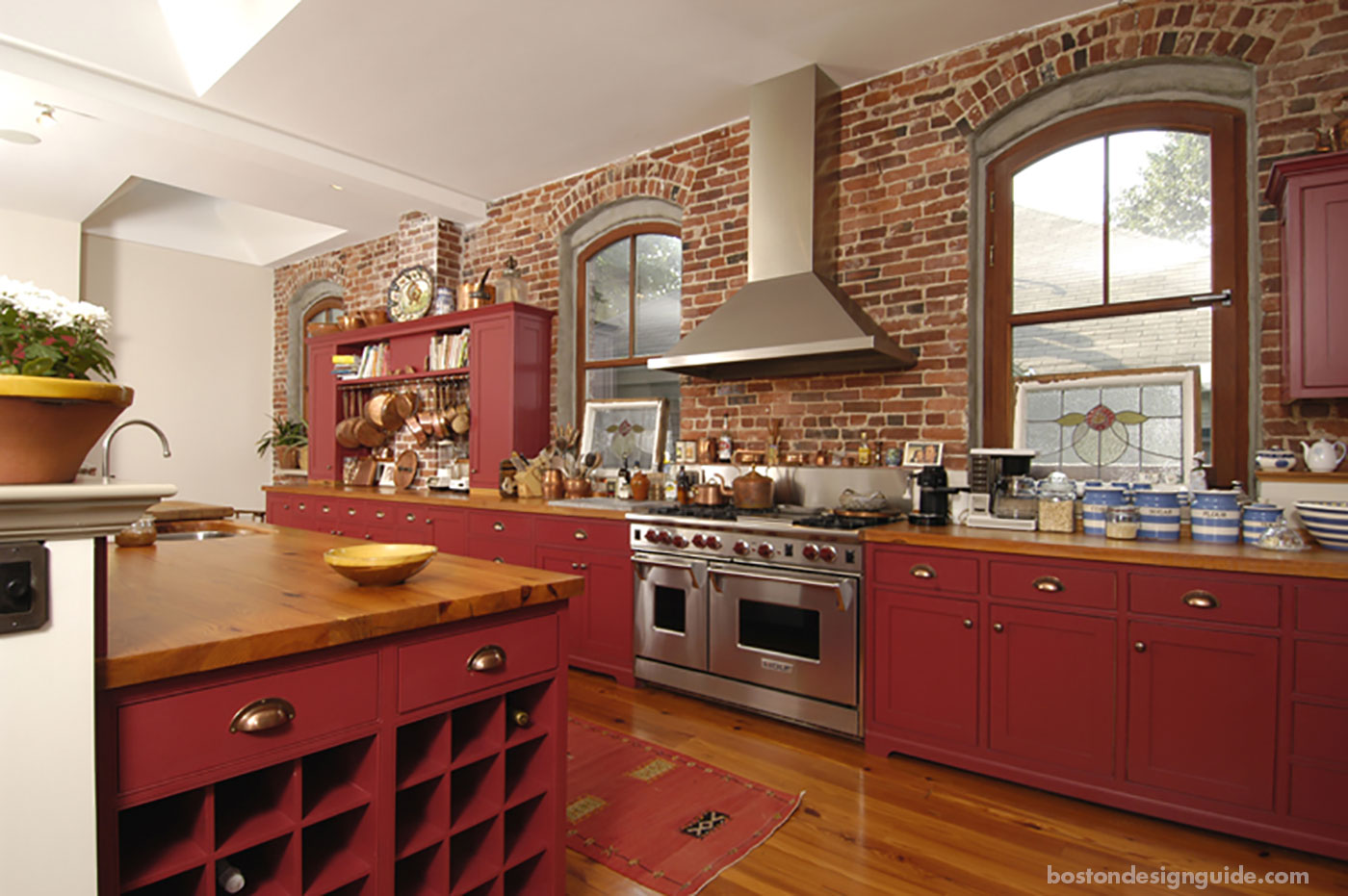Red kitchen renovation with exposed brick by S+H Construction