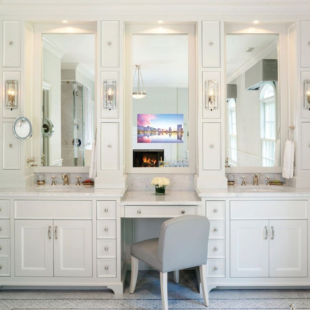 Vanity and sink area of a white bathroom with a television set in the mirror