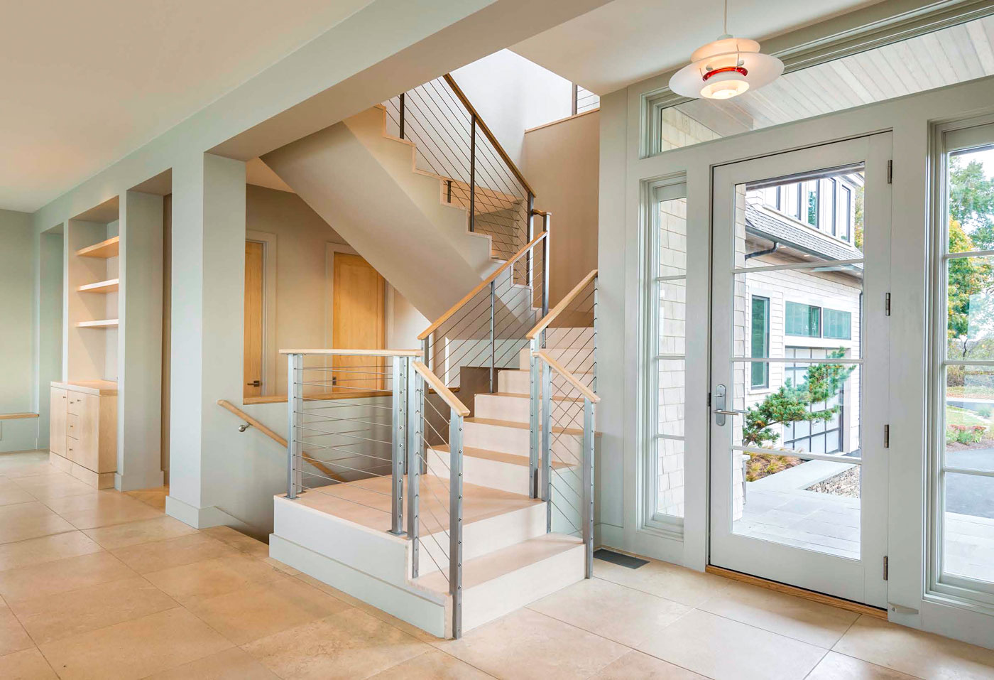 front entry of home with glass doors, tiled floor and stairway