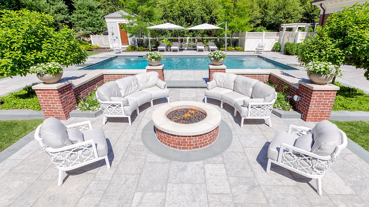 Limestone and brick pool and fire pit terrace by the Schumacher Companies