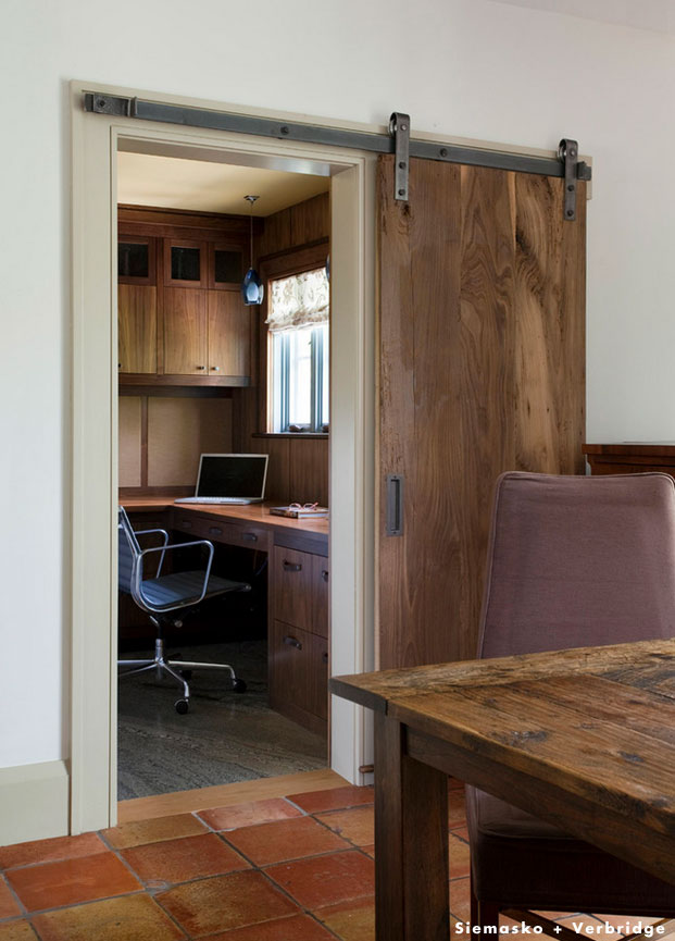 sliding barn doors to a home office complete the rustic style of this