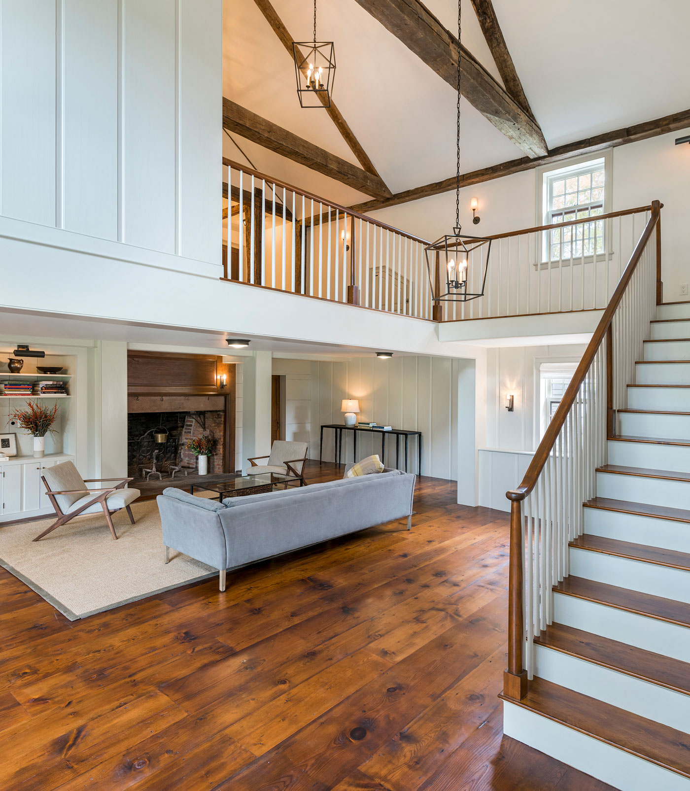 custom living area with vaulted ceilings and a stairway that leads to open second floor