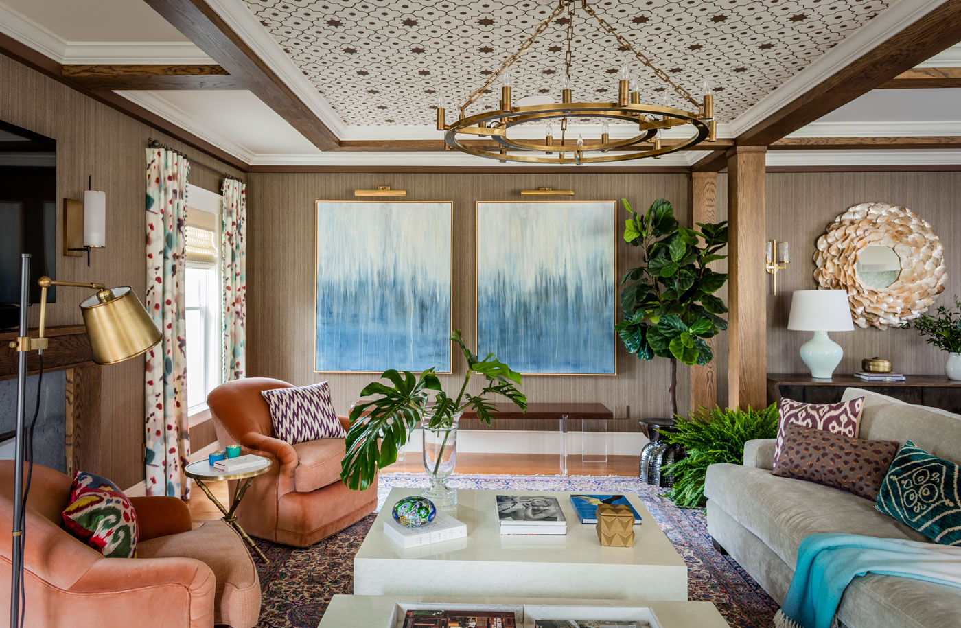 Redesigned Family room with custom ceiling blue abstract paintings on the wall and coral chairs