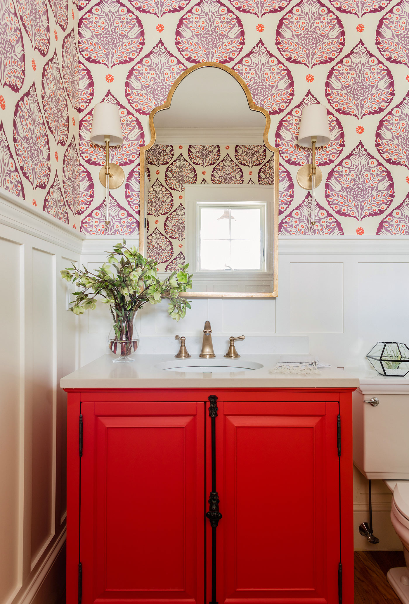 Colorful powder room with red cabinet doors and white paneled walls