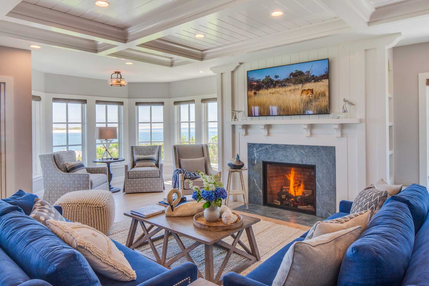 Family room with a fire burning, views of the ocean, blue sofas and custom ceiling
