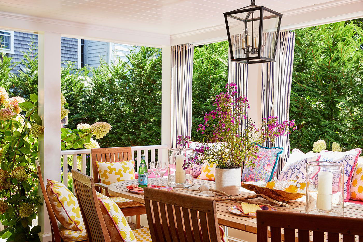 Porch with table and chairs surrounded by lush plantings