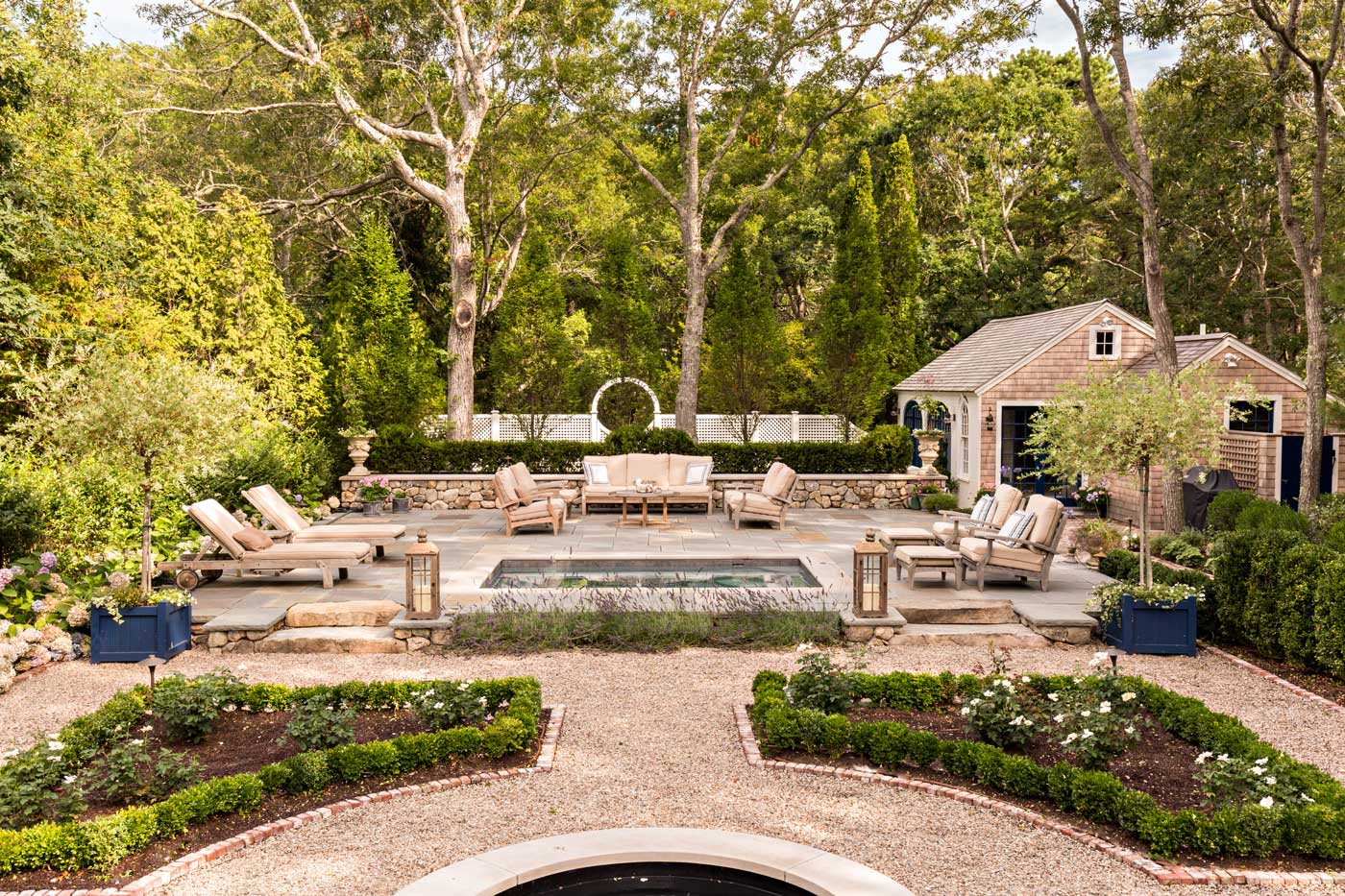 Backyard withreflecting pool and water feature are accented by stonewalls and parterre gardens with boxwoods and roses