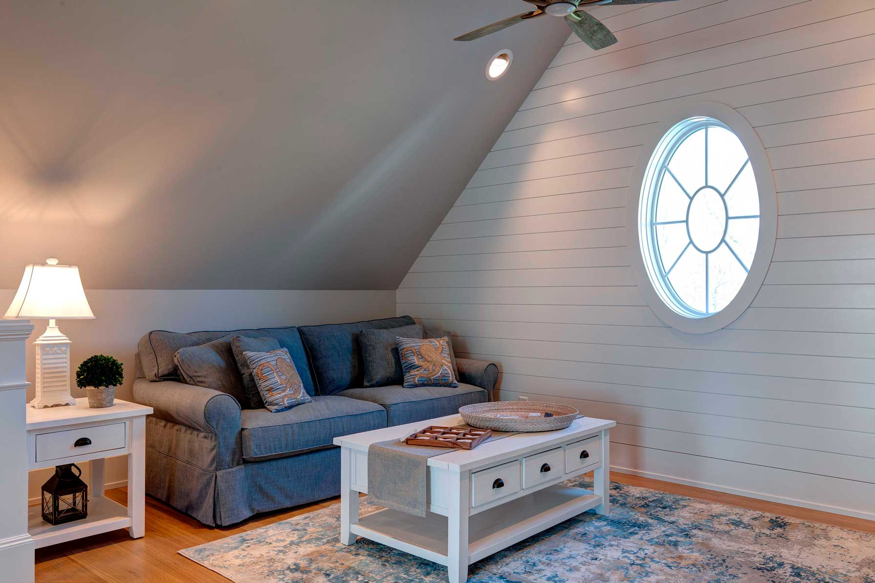 Living area with blue sofa and shiplap walls and circular window