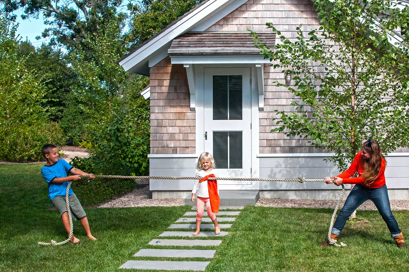 woman playing tug a war with kids