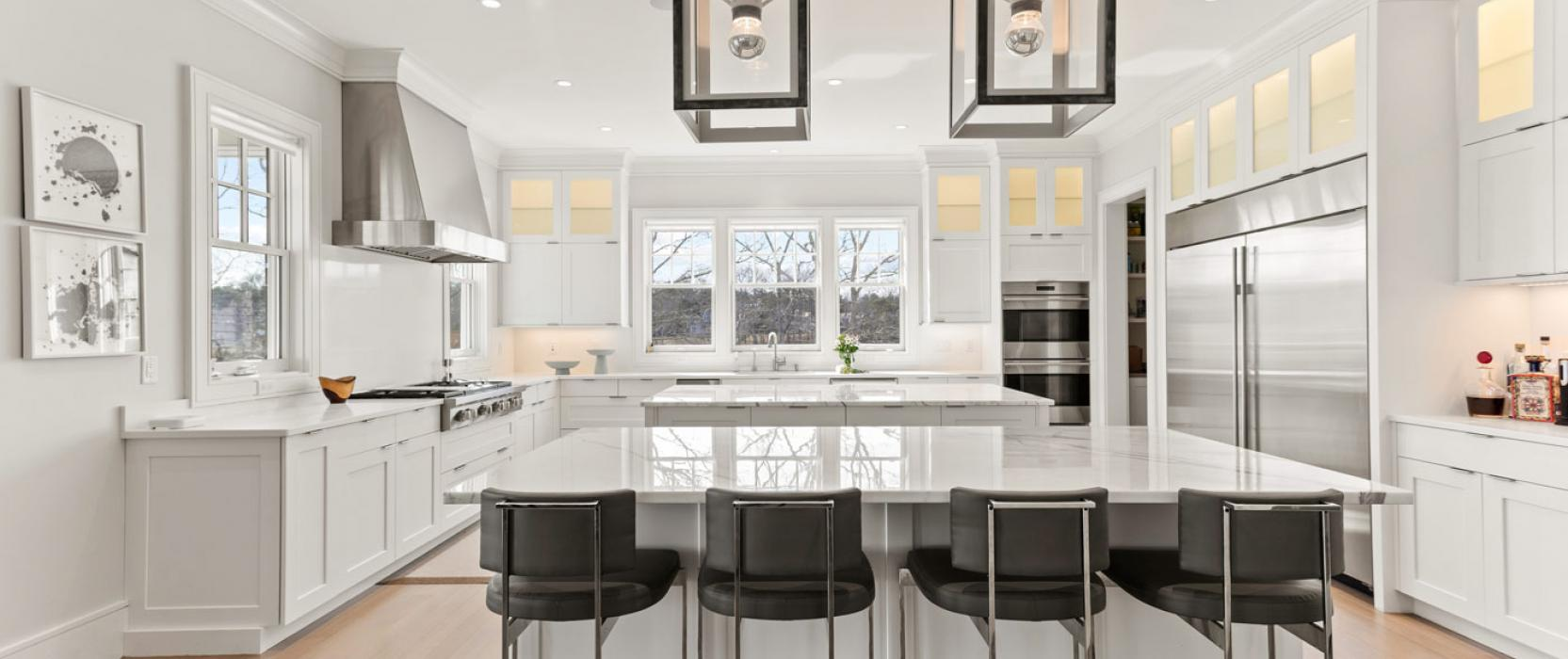 modern white kitchen with 2 big stone islands in the center