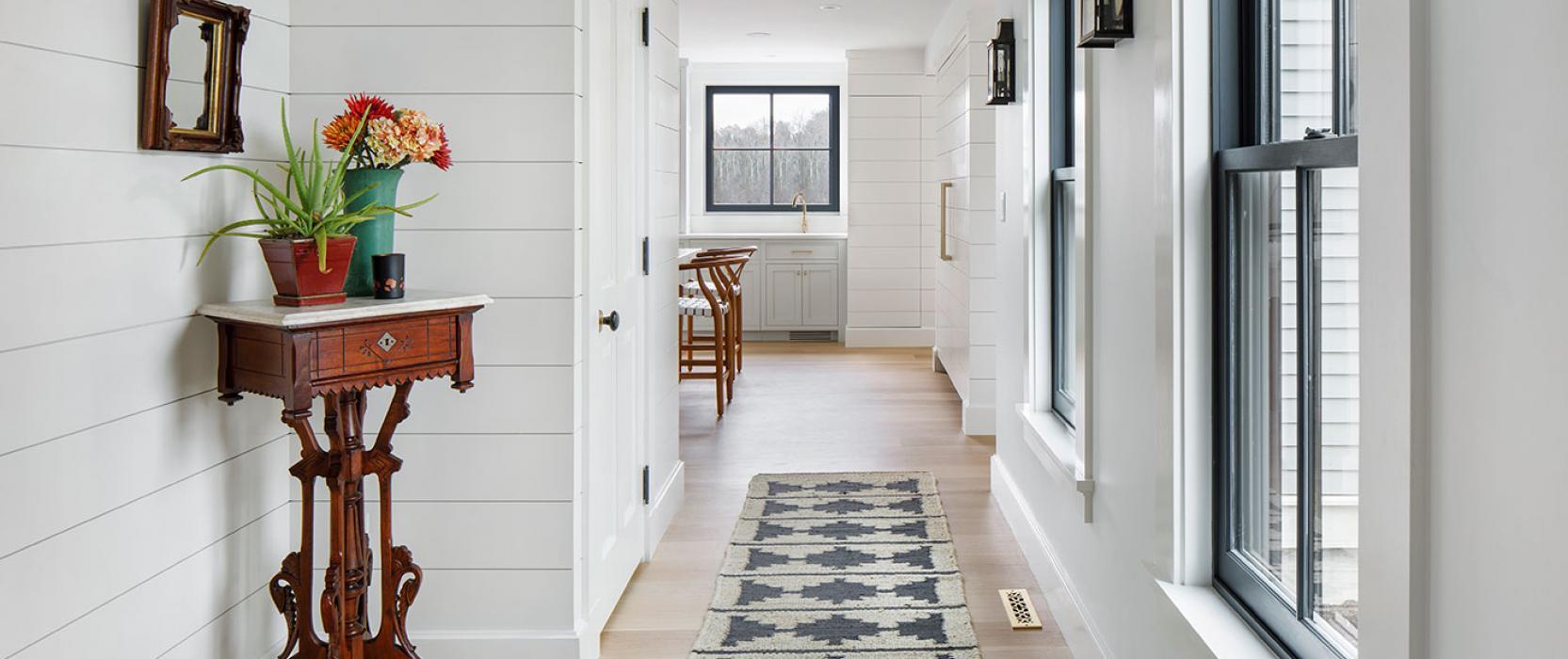 Nickel gap wood paneling lines a custom hallway by McCormack Builders