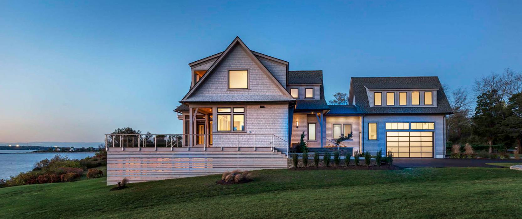 side view of custom home on the water at dusk
