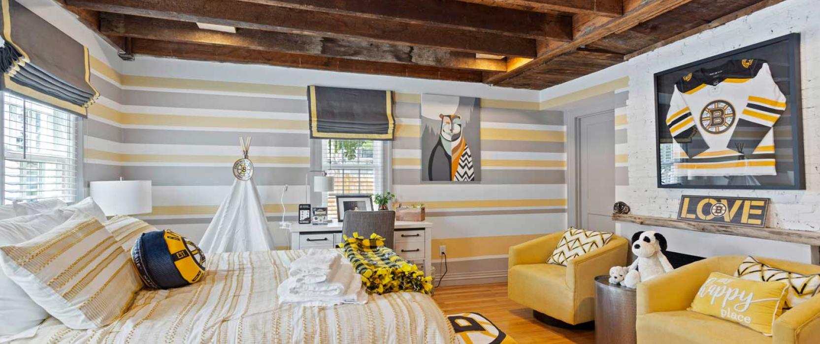 bedroom with wood ceiling and bruins jersey on the wall