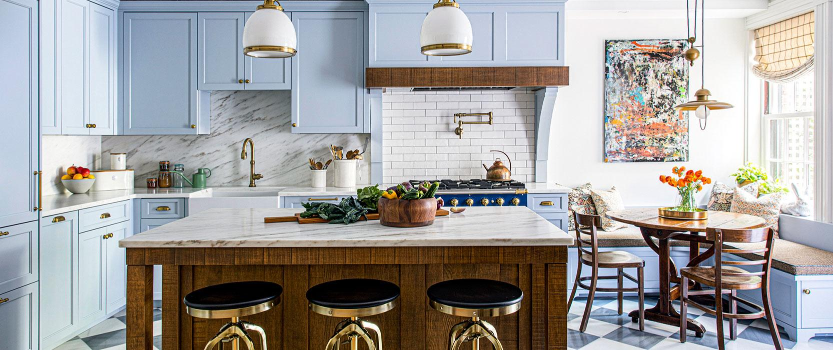 Pale blue kitchen with black and white tiled flooring and colorful art hanging over the breakfast nook