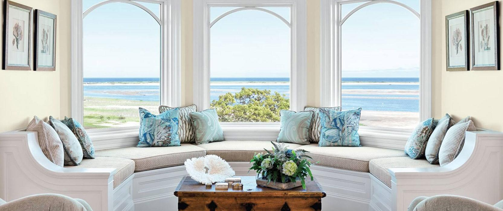Window seat with custom upholstered pillows in a bay window with a view of the water