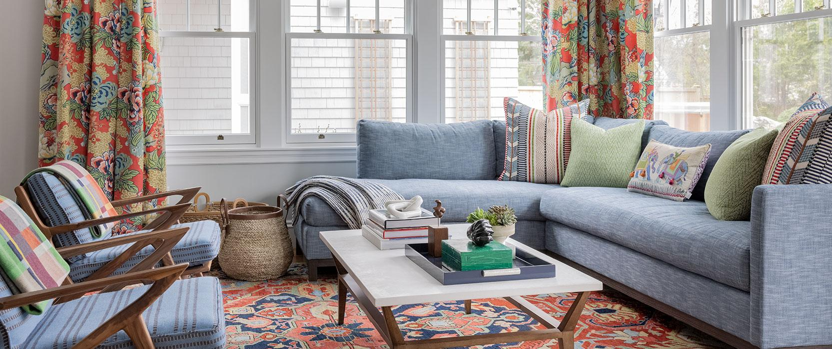 living room with light blue sofas and colorful curtains