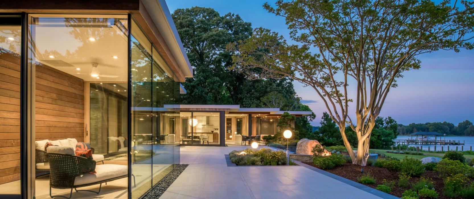 Custom home with floor to ceiling windows overlooking the water