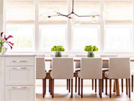 Kitchen table with greenery on top and wall of windows