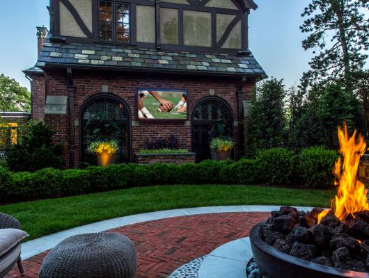 Landscape design featuring an outdoor TV, with home integration by Creative Systems