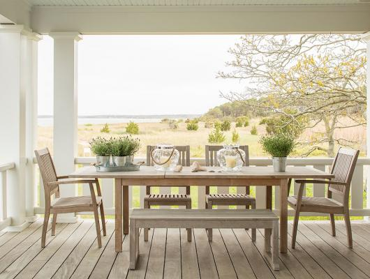 Teak table and chairs on a deck overlooking the ocean and marsh