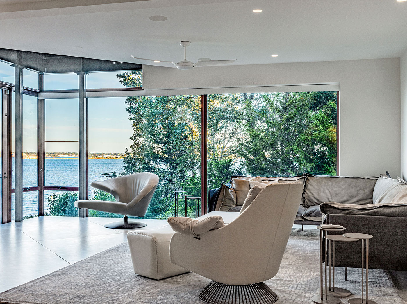 Modern living room with panoramic coastal views by Divine Design Center