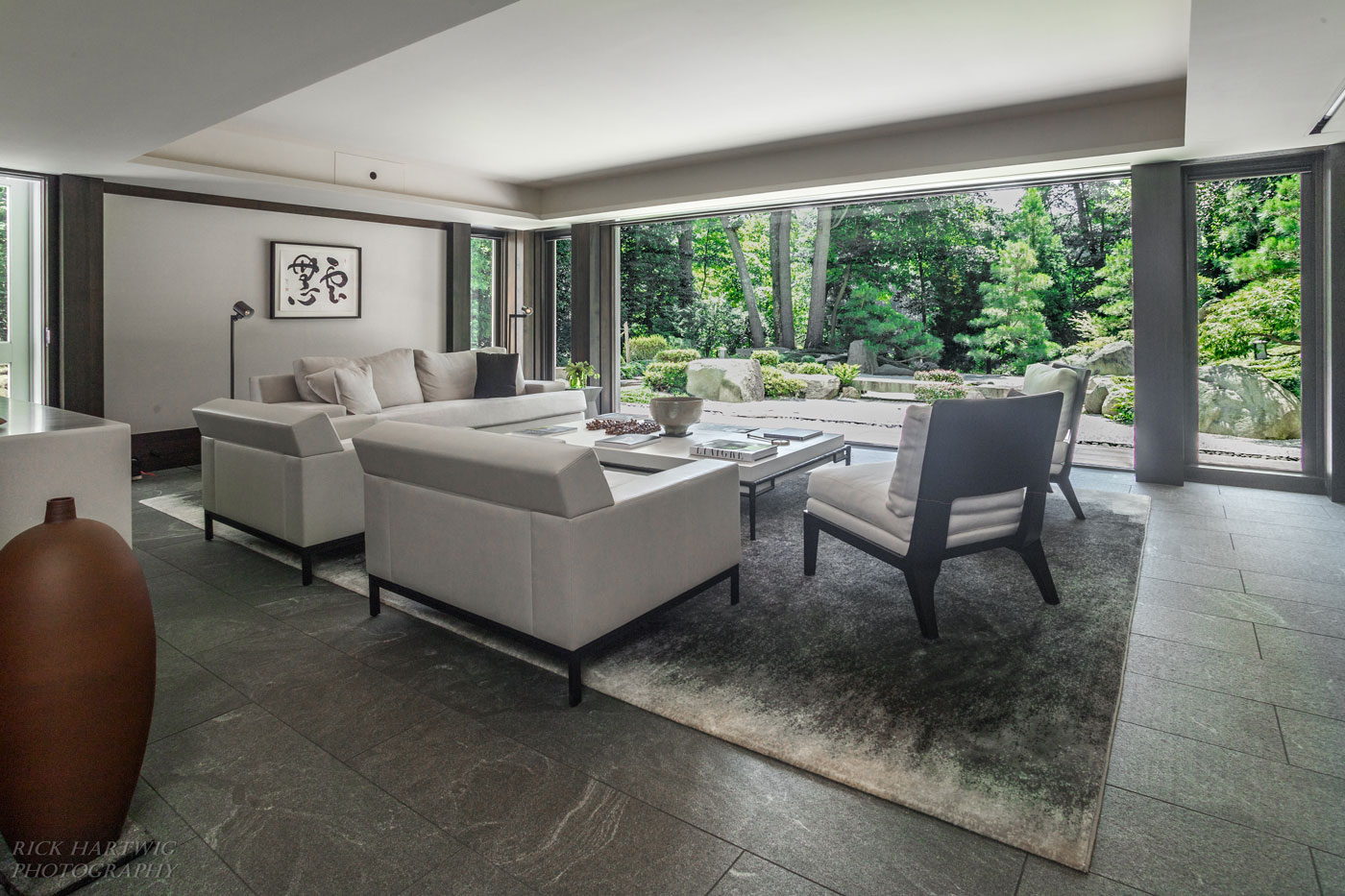 Serene living area with floor to ceiling windows looking out into nature