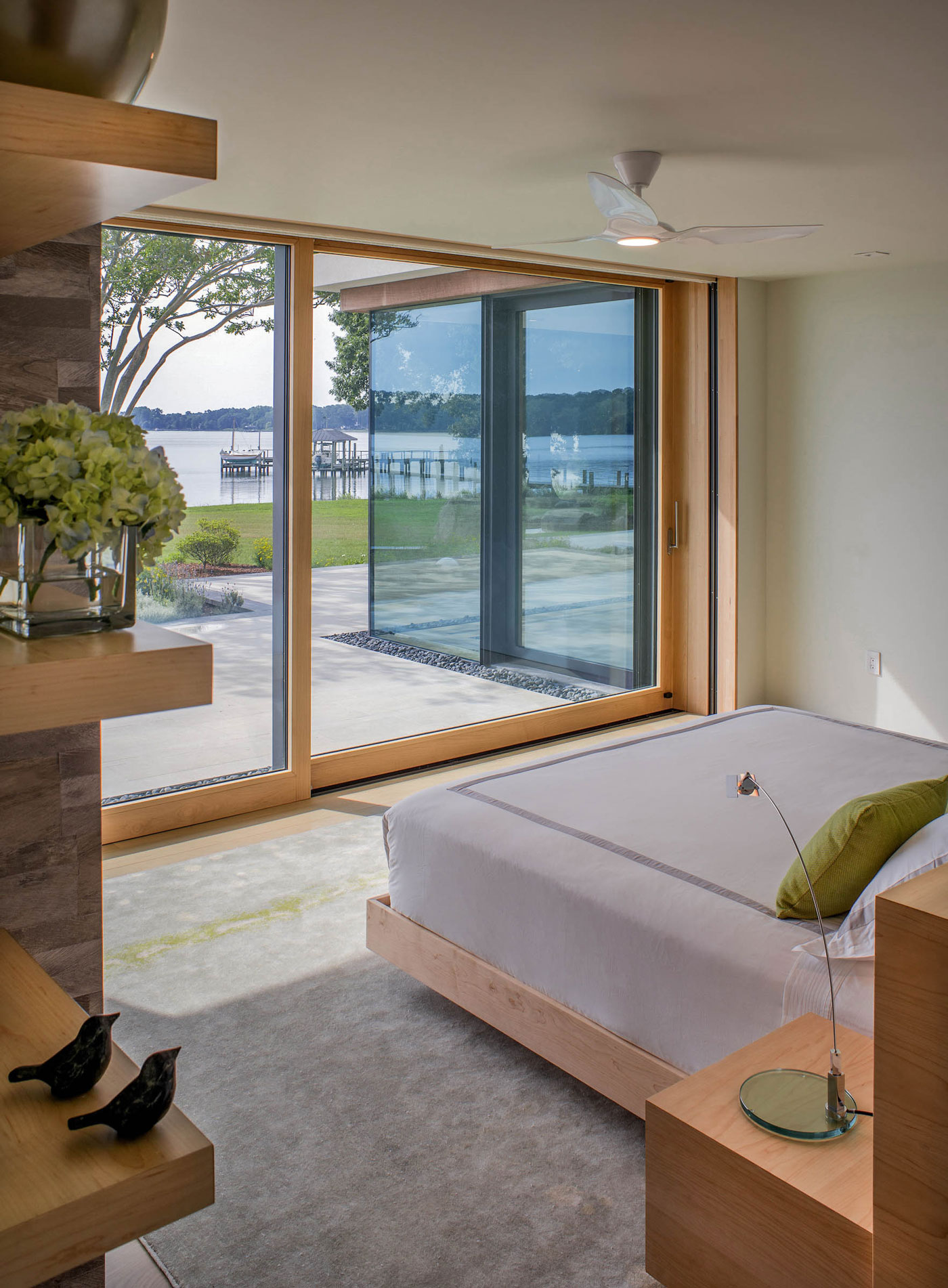 Bedroom with full length windows overlooking the water